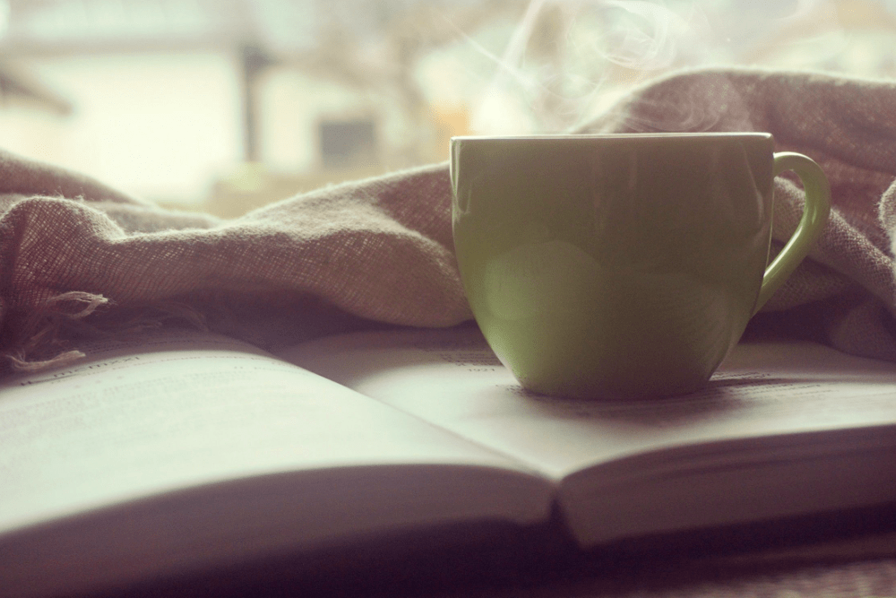 Reading a book while enjoying a coffee